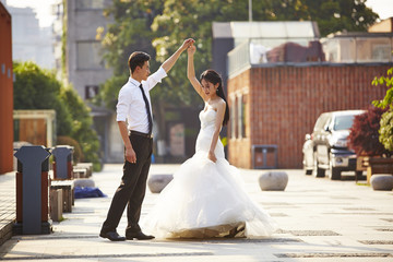 asian bride and groom dancing in parking lot