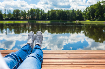 Woman relaxing her feet by the lake.