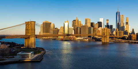 Fotomurales - Sunrise on the Brooklyn Bridge, the East River and the skyscrapers of Lower Manhattan (panoramic). New York City
