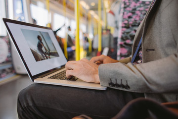 Young business man working in a train - closeup on his hands on laptop