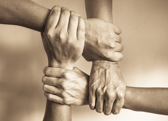 Stack of hands showing unity and teamwork. People helping each other.