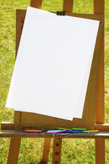 Wooden easel with white paper and crayons on green grass, sunny day outside.