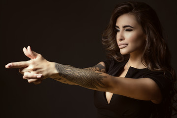 Portrait of young beautiful tattooed woman with luxuriant shining wavy hair and perfect make up pretending to aim something with shooting gesture of her hands. Studio shot. Copy space