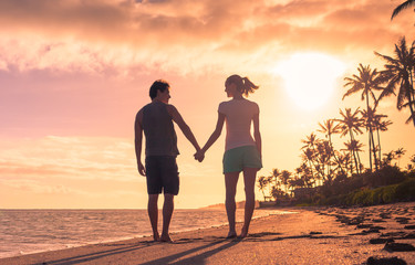 Young couple holding hands walking on the beach at sunset.