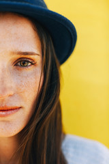 Half portrait of a beautiful woman in front a yellow wall.