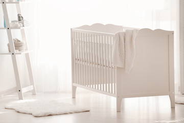 Beautiful light room with crib and toys on shelves