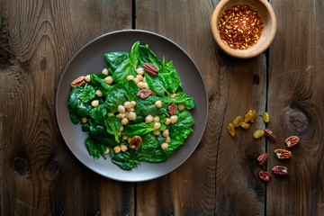 Food: spinach salad with chickpea, pecans and raisins
