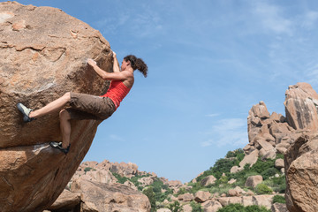 Young woman rock climbing to the top of a boulder