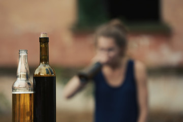 Poster de jardin Bar Bottles with alcohol on blurred view of drunk woman