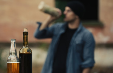 Bottles with alcohol on blurred view of drunk man