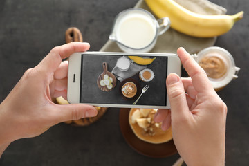 Woman taking photo of delicious food with mobile phone