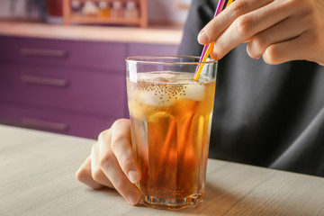 Woman holding glass of tea with chia seeds on table