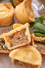 Delicious little meat pies on wicker tray