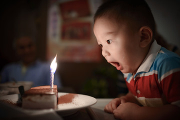 Asian Boy Amazed with Candles on Cake