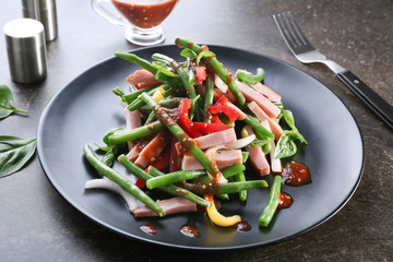 Plate with delicious green beans salad on kitchen table
