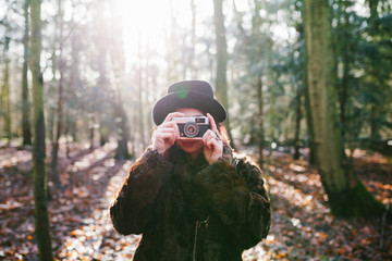 Young woman with a hat and a coat making photos with a camera in the forest