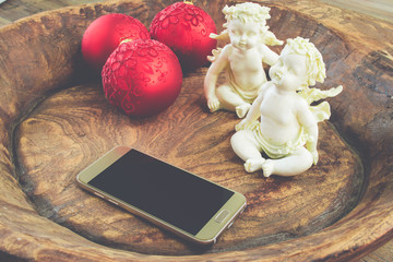 Christmas home concept with white angels, red baubles and smartphone on decorative rustic wooden bowl. Vintage style.