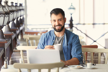 Young blogger drinking coffee and using laptop in cafe outdoors