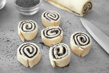 Raw rolls with poppy seeds on table