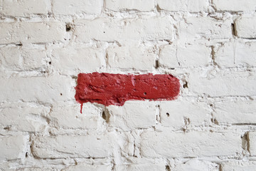 red painted line on a white brick wall