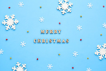 A xmas card. Christmas pattern of small and large white snowflakes, yellow and red bells with the inscription Merry Christmas on a blue background. Winter concept