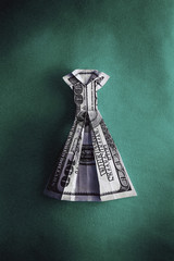 An origami dress made from hundred US dollar bill on green background