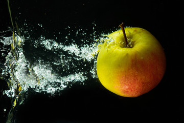 A red-green apple in a stream of water