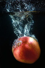 A red apple in a stream of water