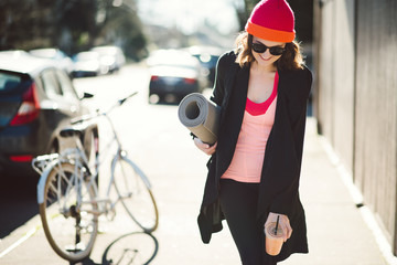 Young woman walking down city street after a yoga class
