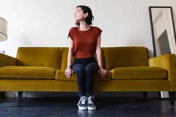 Beautiful brunette sitting on the sofa indoors
