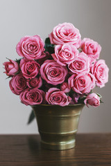 Bouquet of a pink roses in a vintage gold vase on a wood table.
