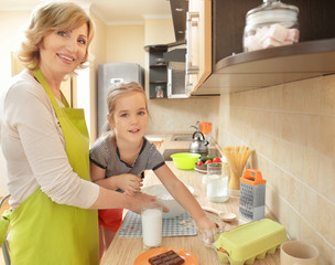 Cute little girl and her grandmother cooking in kitchen