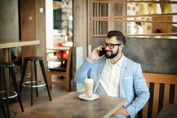 Handsome successful businessman talking on mobile phone in cafe
