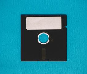 Old floppy disk sitting on a blue background.