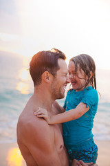 Young dad having fun laughing with his daughter on tropical beach at sunset