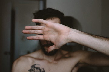 Portrait of a Man with Tattoo Blocking Camera With Hand