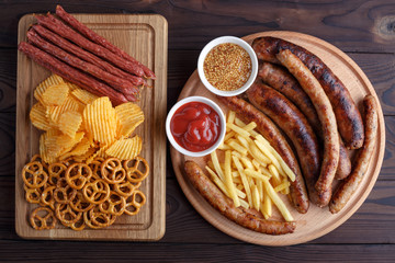 Appetizing beer snacks set for big company of friends. Grilled sausages and french fries with spicy tomato sauce and mustard, pretzel crackers, chips and salami on the board. Oktoberfest, pub concept