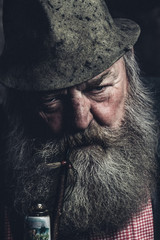 portrait of an angry looking full bearded old man with a pipe and a millinery