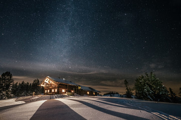 alpine cabin in snowy mountain landscape at night under the milky way
