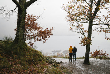 Young couple in waterproof clothing admiring viewpoint over lake in the rain.
