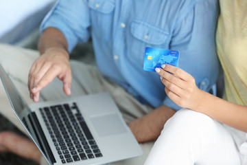 Couple with laptop and credit card. Internet shopping concept