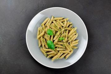 Pasta with homemade pesto sauce in a gray plate on a dark stone slate background, top view, copy space
