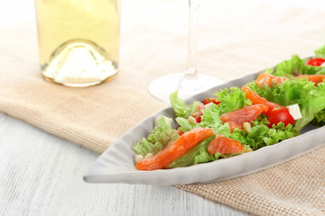Plate with delicious salmon salad on table