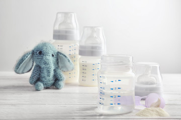 Bottle of water and powder for preparing baby milk formula on wooden table