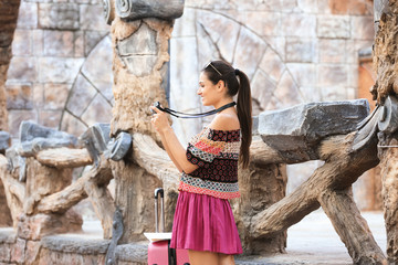 Beautiful young tourist with camera and suitcase standing near ancient wooden fence