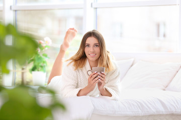 Young woman with cup of morning coffee on bed at home