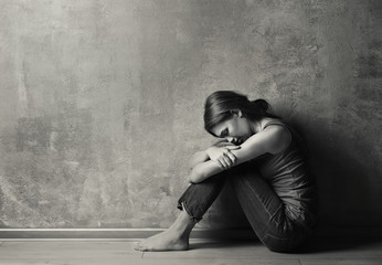 Battered young woman sitting near concrete wall