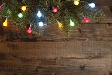 Colorful christmas lights with pine branch on wooden background
