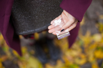 A girl is holding a packet of drugs in a plastic bag. Drugs in the school.