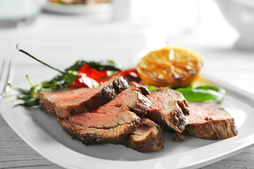 Plate with sliced delicious steak and vegetables on table